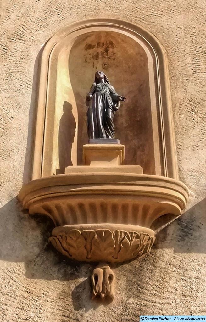 La statue se trouvant dans la niche à gauche de la porte