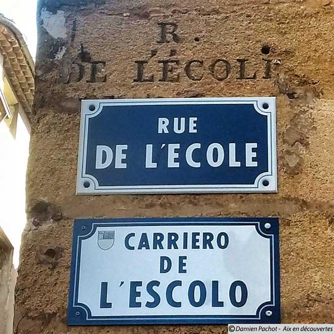 """Le mot """"rue"""" est tronqué sur l'inscription en pierre de taille indiquant la rue de l'Ecole"""